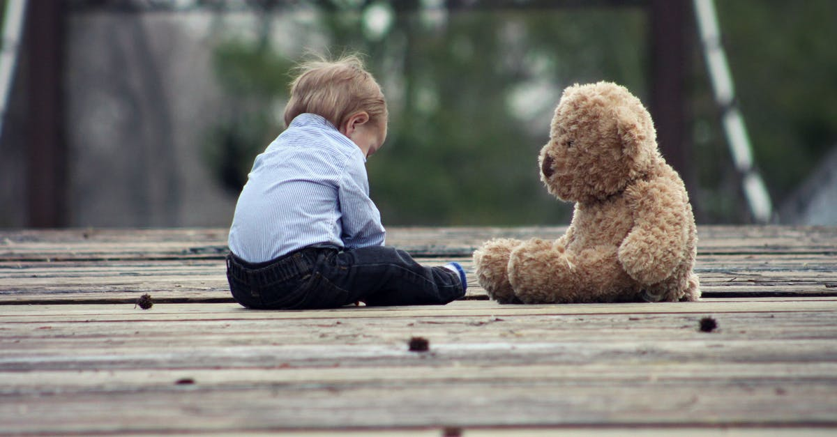 A brown teddy bear sitting on top of a wooden bench